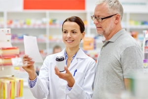 pharmacist and elderly man checking a prescription